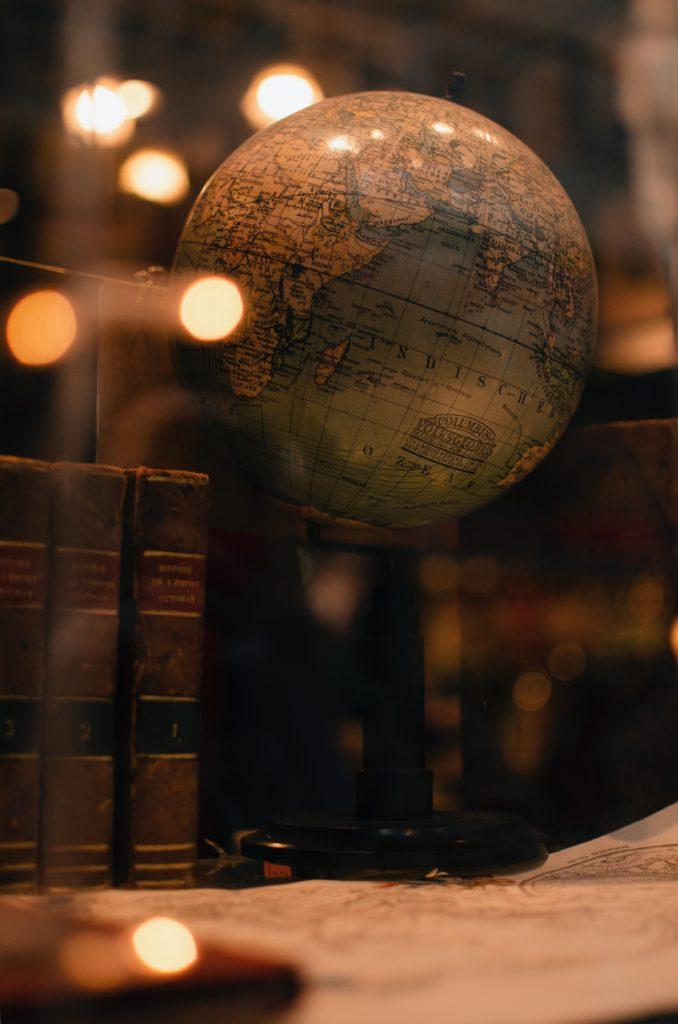 Close up of a globe on a bookshelf.
