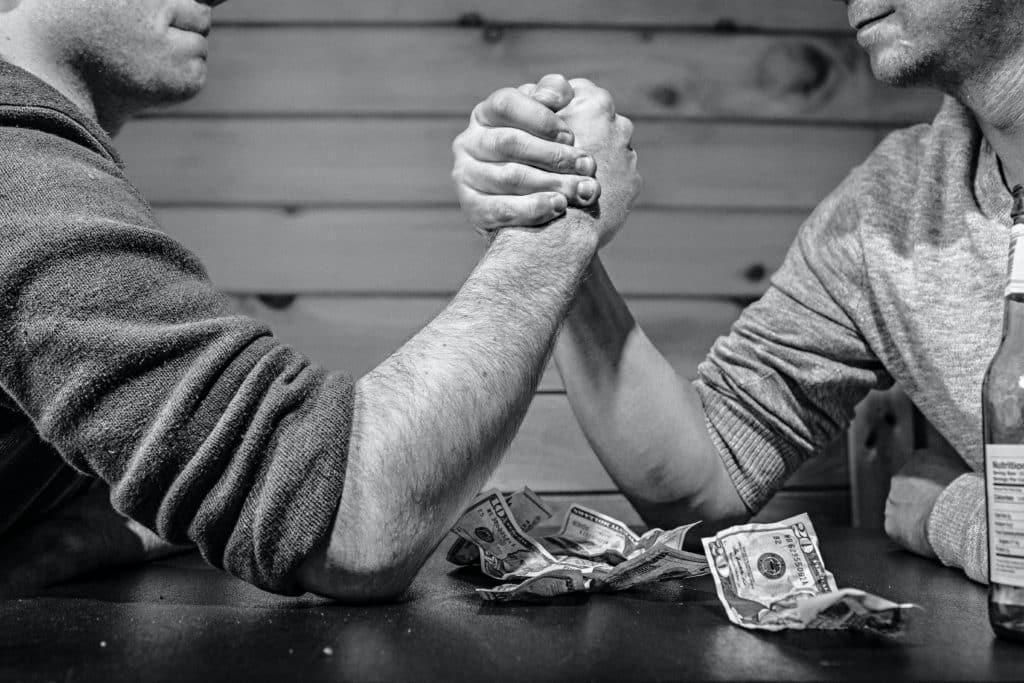 Two men arm wrestling over money.