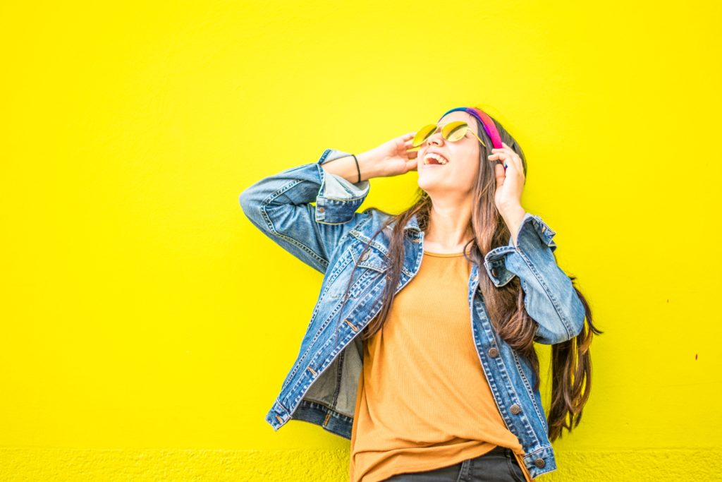 Stylish girl in front of a bright yellow background.