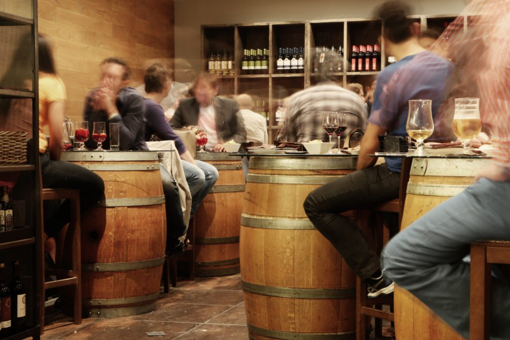 People sitting around barrels at a brewery/winery.