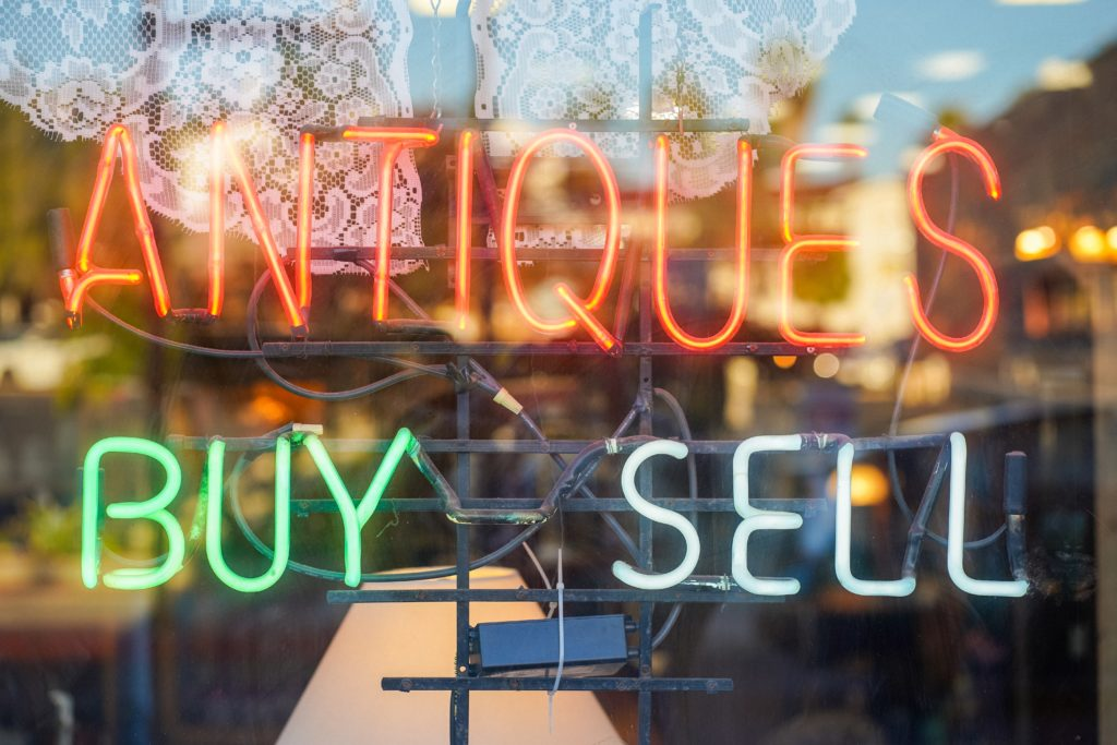 """A neon sign that reads """"Antiques Buy Sell"""""""
