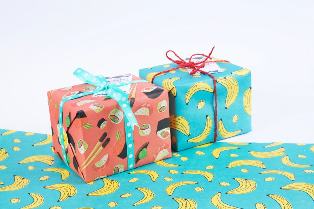 Two presents wrapped in sushi and banana wrapping paper.