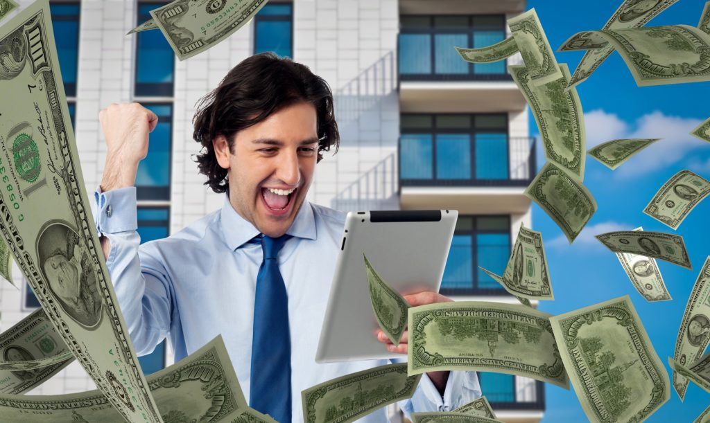 Man looking at tablet with money flying around him.