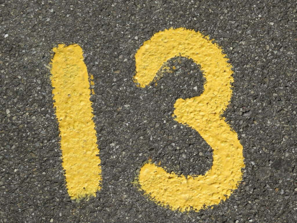 The number 13 painted in yellow on concrete