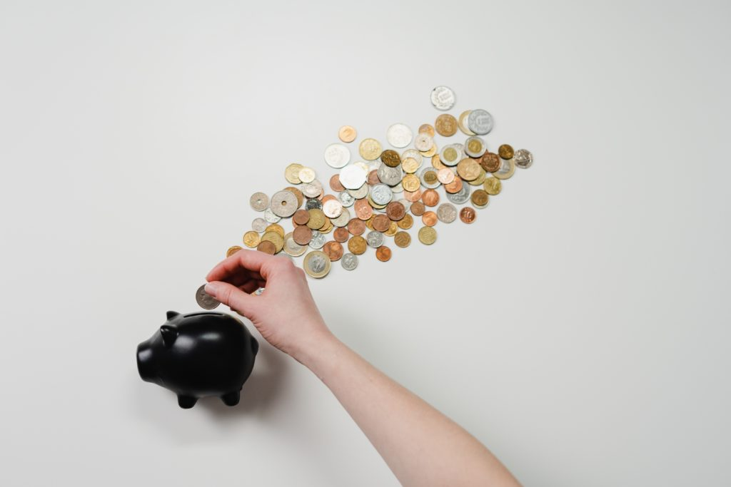 Coins being dropped into a small black piggy bank.