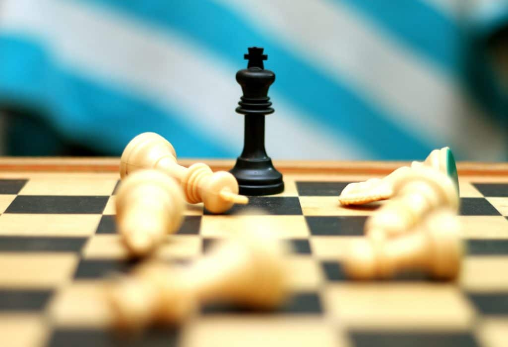 A black king chess piece among fallen white pieces on a chessboard