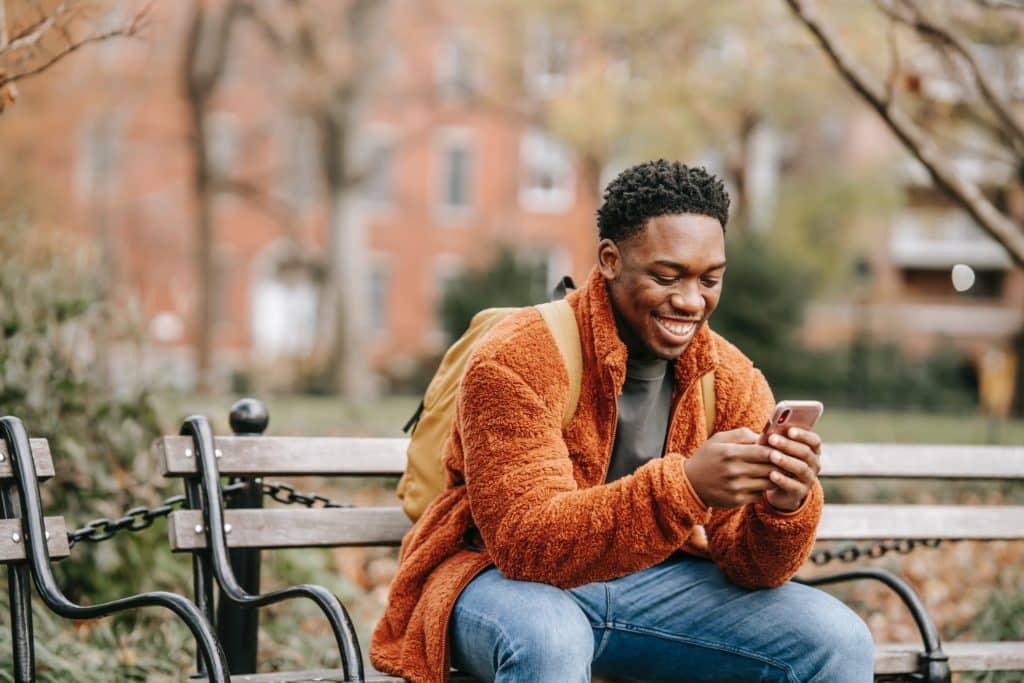 Man in orange jacket smiling while looking at phone.