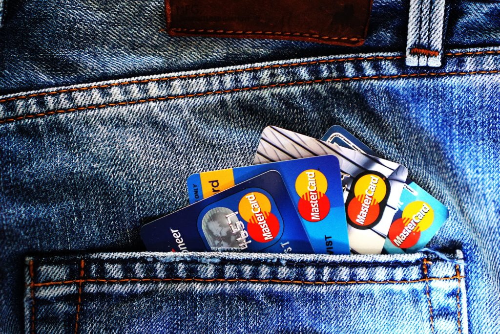Back pocket of jeans filled with gift cards.