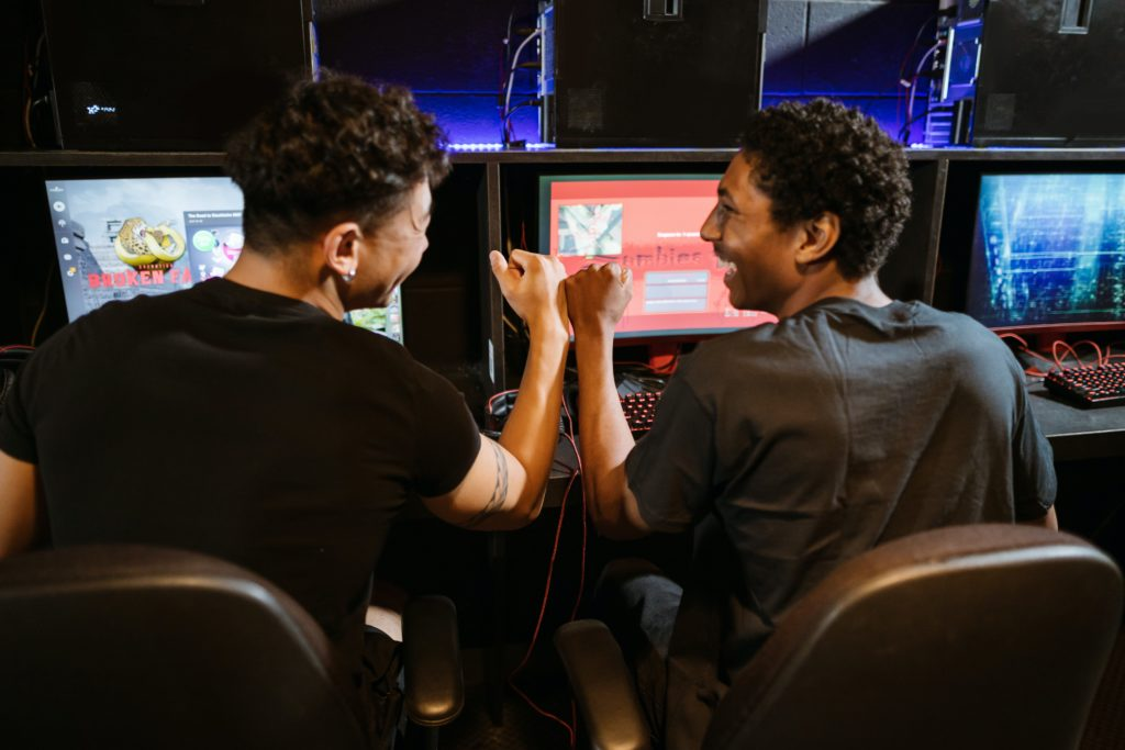 Two men fist bumping in front of computer screens.