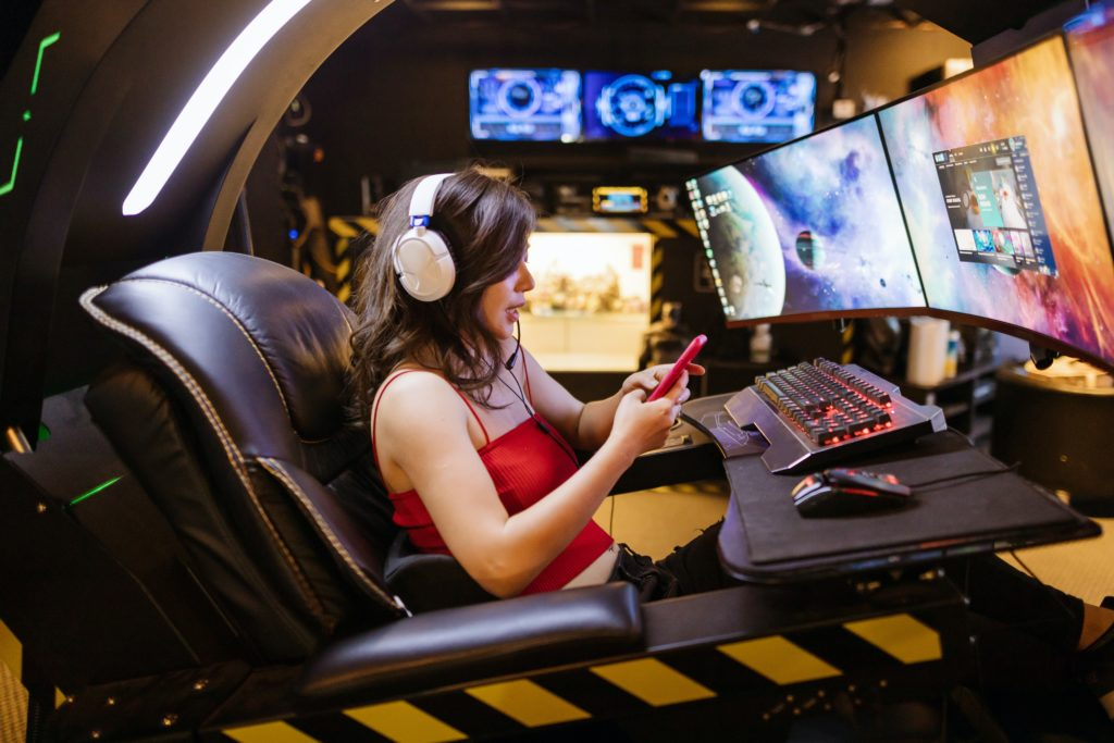 Gamer girl playing on phone in front of computer screens.