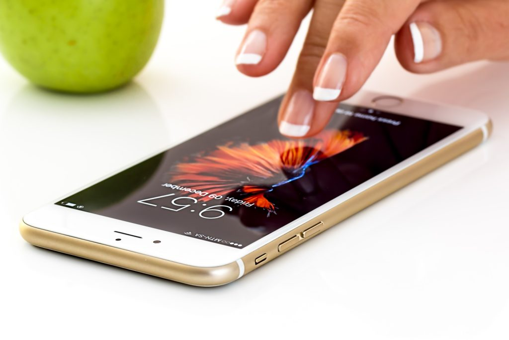 Woman's fingers touching a smartphone screen.