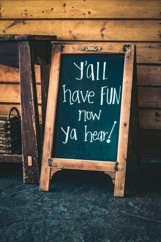 "A chalkboard sign that reads ""Y'all have fun now ya hear?"""