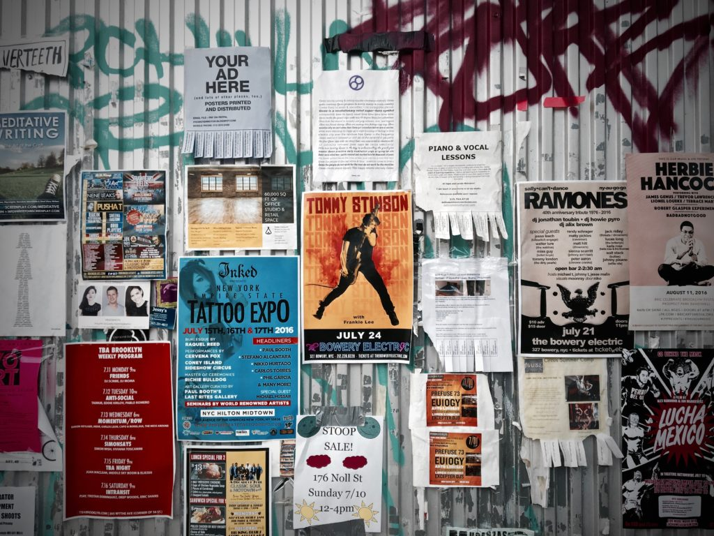 Wall with various posters and flyers on it.