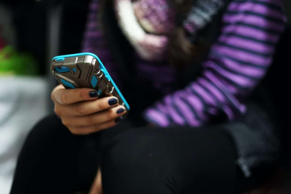 Woman in purple and black striped shirt holding a blue smartphone.