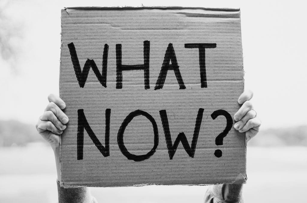 """Black and white photo of a person holding up a sign that reads """"What Now?"""""""