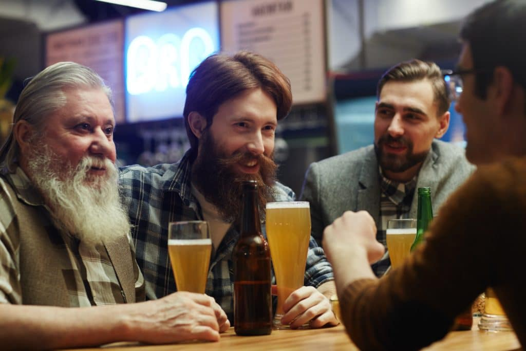 A group of men drinking beer at a bar.