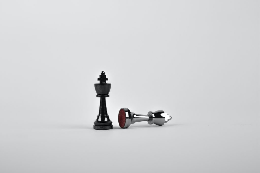 Black King and fallen White King chess piece.