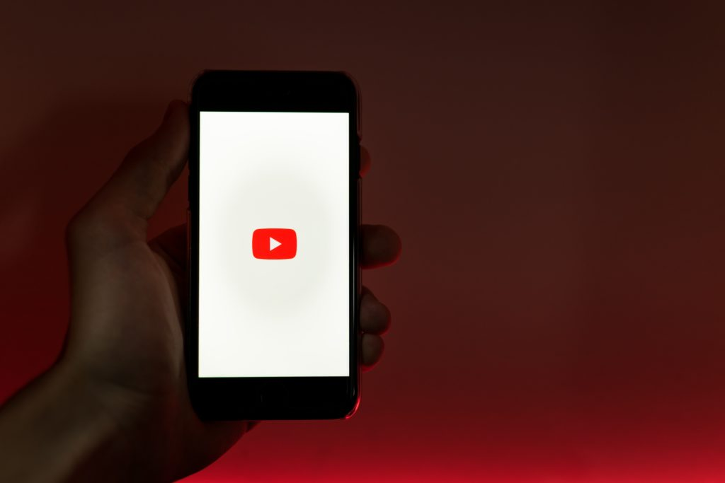 Hand holding a phone displaying the YouTube app against a red background.