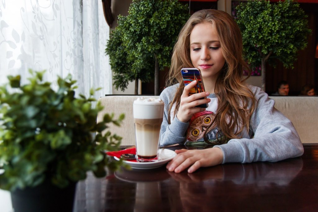 A teenage girl looking at her smartphone with an iced latte.