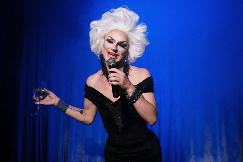 Drag queen holding a drink in one hand and a microphone in the other.