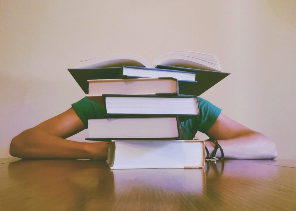 Girl behind a pile of books.