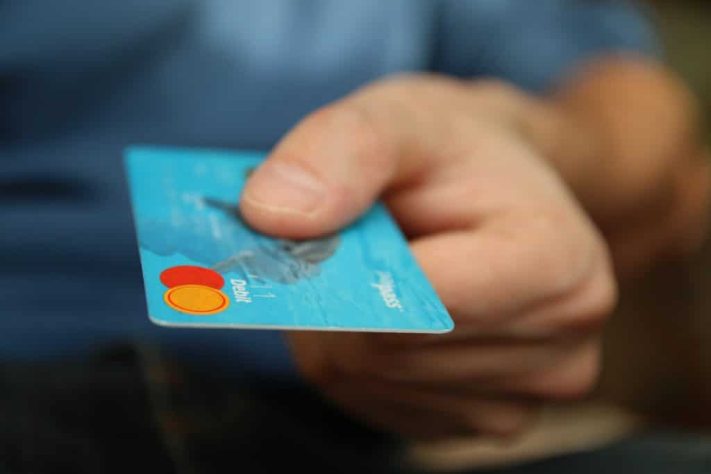 Close up of a hand holding a debit card