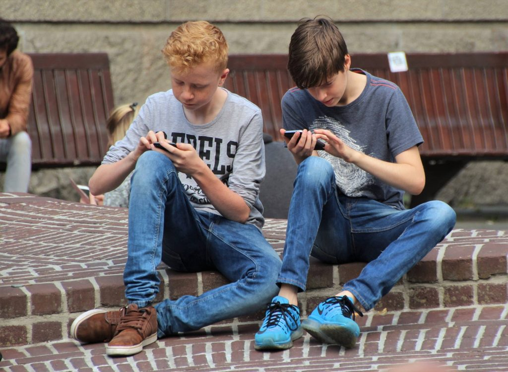 Two young boys playing on smartphones.