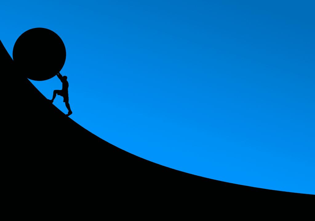 Man pushing a ball up a hill.