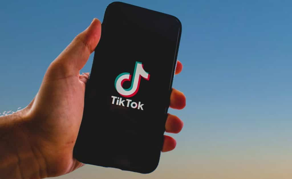 A man's hand holding a phone displaying the TikTok start up screen.