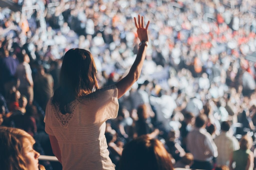 A girl waving in a large crowd.