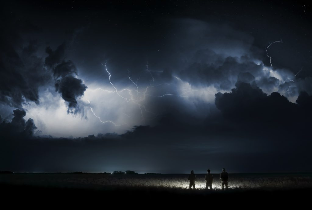 A dark sky with lightning above three men in a field.